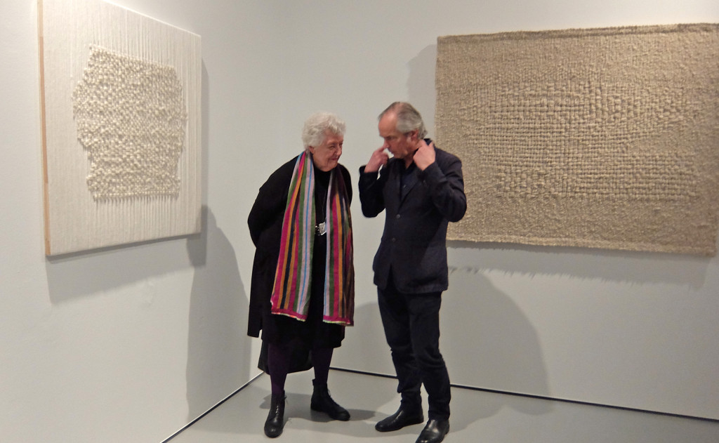 "Sheila Hicks with visitor; to the left ""Conversation"", 2016; to the right ""White letter II"", 1961, collection Stedelijk Museum Amsterdam; Hicks calls her experimental monochrome tapestries ""Hieroglyphs and letters"""