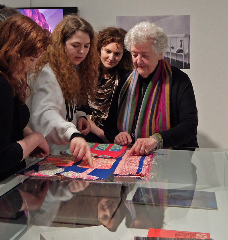 "Sheila Hicks with students at her exhibition ""Why Not"""